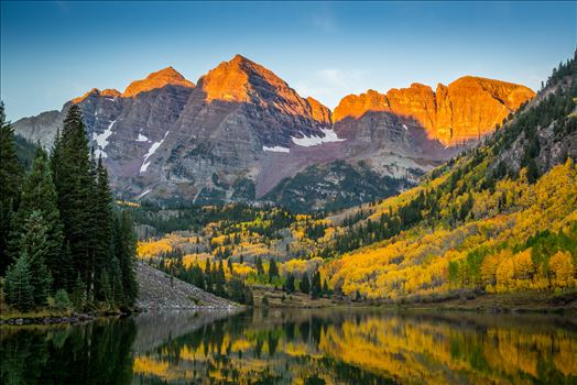 The rising sun lights the peaks of the Maroon Bells.