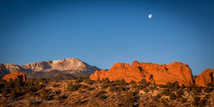 The moon sets as the morning sun lights up the Garden of the Gods and Pike's Peak in Manitou Springs, Colorado.