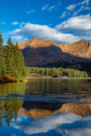 Lake Irwin reflects the Ruby Range mountains just after sunrise near Kebler Pass,  Colorado.